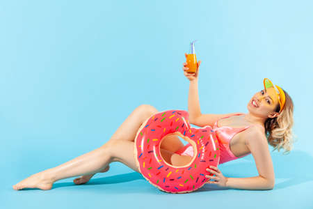 Portrait of cheerful smiling woman in swimsuit covering eyes with fresh cut orange, having fun. Concept of female beauty and skin care, natural cosmetic antioxidant. indoor studio shot isolated 免版税图像