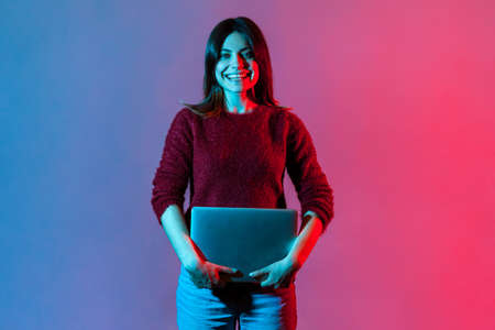 Portrait of successful happy office worker, pretty girl in casual pullover standing, holding closed laptop or folder, looking at camera with toothy smile, positive expression. neon light, studio shot 免版税图像