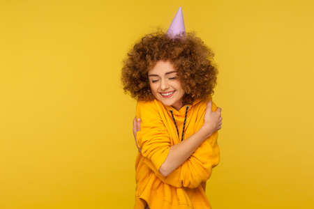 Portrait of funny cheerful curly-haired woman in urban style hoodie pointing at blue gift box and looking at camera with excited smile, boasting present. studio shot isolated on yellow background Stock Photo