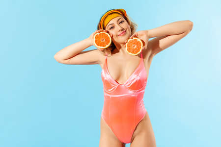 Portrait of lovely carefree beautiful woman in swimsuit holding rubber ring and sweet lollipop candy, enjoying rest on tropical beach, vacation resort. indoor studio shot isolated on blue background