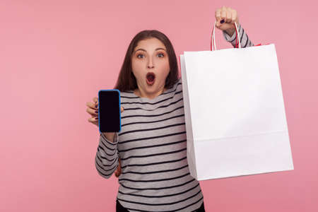 Portrait of optimistic happy woman in striped sweatshirt showing double victory gesture, peace hand sign, celebrating victory, glad about success. indoor studio shot isolated on pink background