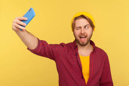 Don't know, who cares! Confused hipster bearded guy in beanie hat and checkered shirt standing with no idea gesture, shrugging shoulders raising hands. indoor studio shot isolated on yellow background Stock fotó