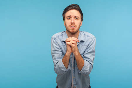 Please, I'm begging! Portrait of unhappy man in worker denim shirt keeping hands in prayer gesture and looking with imploring expression, sincere asking permission. indoor studio shot, blue background