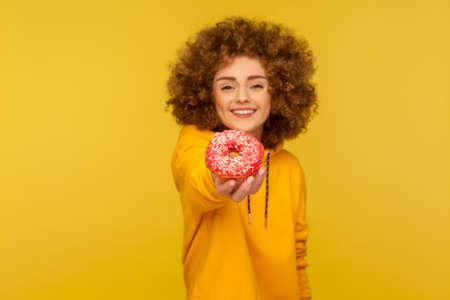 Take sweet dessert! Portrait of happy curly-haired young woman in urban style hoodie giving delicious sugary donut and smiling genuinely to camera. indoor studio shot isolated on yellow background