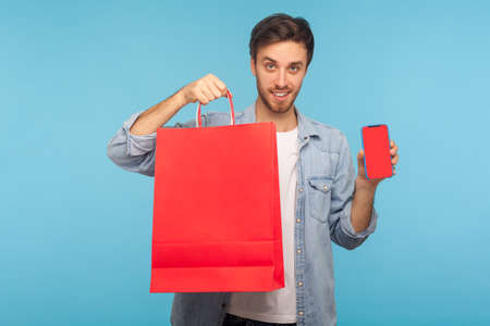 Portrait of generous kind cheerful man with party cone hat giving gift, congratulating on birthday and offering surprise, holiday bonus wrapped in box. indoor studio shot isolated on blue background