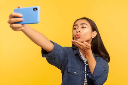 Hey you! Portrait of playful girl in denim shirt pointing to camera and showing heart Like icon, follower notification symbol, click button for social media. studio shot isolated on yellow background