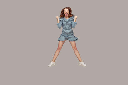 Wow, oh my god! Surprised excited brunette girl ruffle blouse looking at camera with amazement, open mouth in astonishment, shocked by unbelievable news. studio shot isolated on gray background