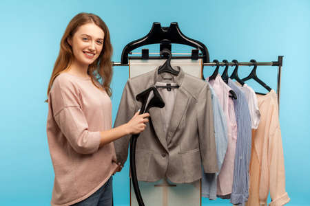 Young happy woman steaming business suit at dry-cleaner and smiling to camera, advertisement of professional services washing, cleaning and ironing clothes, care of fabric. indoor studio shot isolated