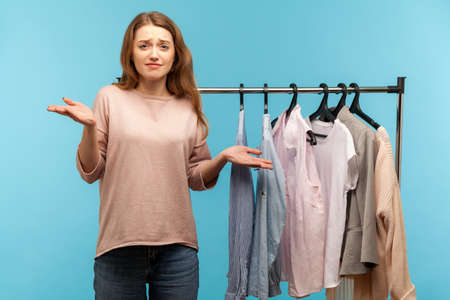 Don't know! Confused clueless woman, fashion stylist gesturing doubt, not sure which clothes to choose, standing near wardrobe with trendy outfit on rack in shop boutique. indoor studio shot isolated
