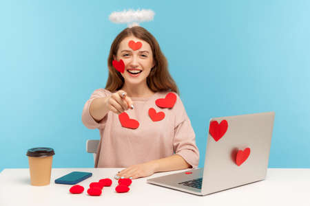 Hey you! Joyful angelic woman with kind expression sitting at workplace, all covered with sticker love hearts, pointing to camera, indicating finger and choosing winner. indoor studio shot, isolated