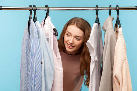 Lovely playful cheerful woman smiling and standing among clothes hang on shelf in designer store, looking around and hiding in wardrobe with trendy outfit on rack. indoor studio shot, isolated