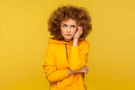 Hmm, need to think! Portrait of confused pensive curly-haired woman in urban style hoodie having doubts while scratching head, thinking intensely. indoor studio shot isolated on yellow background