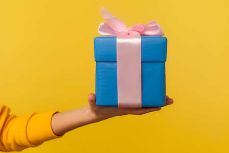 Closeup hand holding blue gift box with pink ribbon decoration, romantic surprise for Valentine's day, nice Christmas holiday present, birthday celebration. studio shot isolated on yellow background Reklamní fotografie