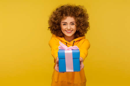 Portrait of funny happy curly-haired woman in urban style hoodie giving blue gift box to camera and smiling, sharing holiday present, congratulating on birthday. indoor studio shot, yellow background 版權商用圖片