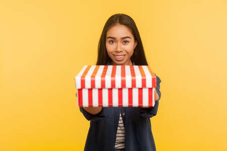 Present for you! Portrait of generous happy brunette girl with charming smile giving box to camera, sharing holiday gift, congratulating on birthday. indoor studio shot isolated on yellow background 版權商用圖片