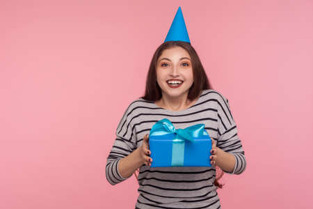 Happy birthday to me! Joyful optimistic woman with party cone hat smiling at camera and holding wrapped gift box, rejoicing present, holiday celebration. studio shot isolated on pink background