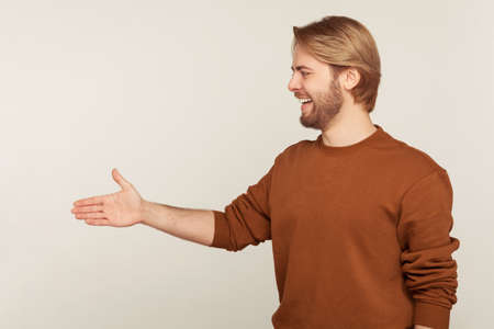 Side view of positive friendly hospitable bearded man in sweatshirt standing with outstretched hand, offering handshake to partner, greeting on job interview. studio shot isolated on gray background