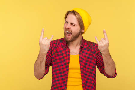 Yeah, this is crazy! Delighted happy hipster bearded guy in beanie hat and checkered shirt shouting excited for success with rock and roll hand gesture. studio shot isolated on yellow background