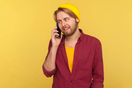 Cheerful trendy guy in hipster beanie hat and checkered shirt calling, smiling while talking mobile phone, having positive conversation on telephone. indoor studio shot isolated on yellow background