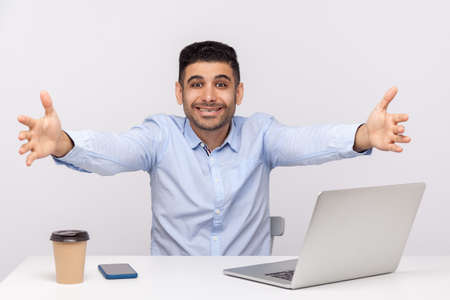 Come into my arms! Excited happy friendly businessman sitting office workplace, stretching hands to camera, going to embrace, welcoming on reception. indoor studio shot isolated on white background 版權商用圖片
