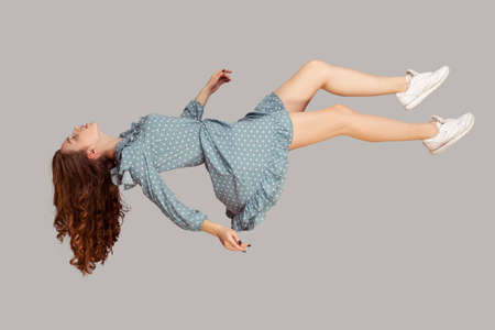Floating in air. Relaxed girl in vintage ruffle dress levitating keeping eyes closed, sleeping while flying mid-air, having comfortable peaceful dream. full length studio shot isolated on gray, indoor