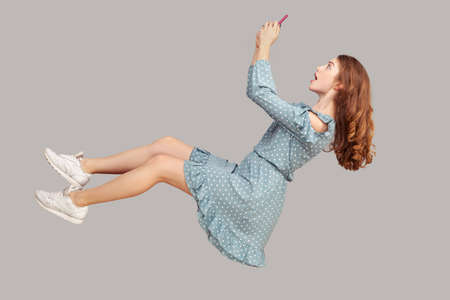 Hovering in air. Surprised shocked girl ruffle dress levitating with mobile phone, chatting online in social network amazed by unbelievable news message, surfing web while flying. studio shot isolated Foto de archivo