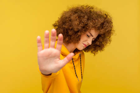I refuse! Portrait of dissatisfied curly-haired woman in urban style hoodie raising palm showing stop gesture, prohibition sign, warning and denying. indoor studio shot isolated on yellow background