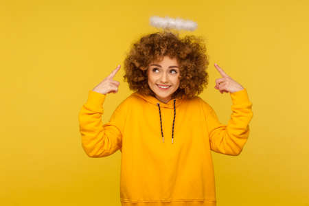 Portrait of charming angel with halo, kind curly-haired hipster woman pointing at saint nimbus over her head and smiling with obedient modest expression. studio shot isolated on yellow background Banque d'images