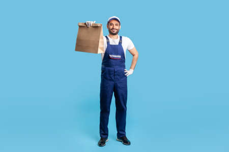 Full length portrait of happy expert courier in blue uniform holding groceries bag and smiling to camera, carrying parcel with goods ordered online. Professional delivery service, food purchase