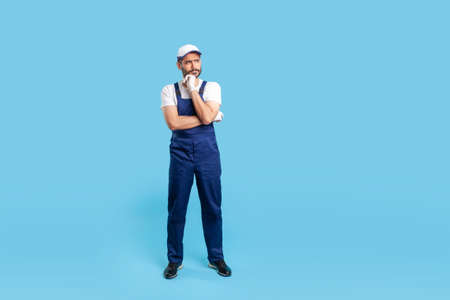 Full body pensive workman in overalls, cap and protective gloves standing, thinking intensely, pondering decision and having doubts. Profession of service industry, house repair. studio shot isolated Imagens