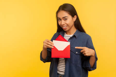 I got love letter on Valentine's day. Happy beautiful girl in denim shirt pointing letter in red envelope, holding greeting card and smiling joyfully. indoor studio shot isolated on yellow background