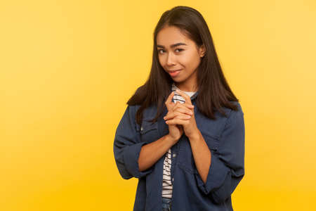 Portrait of sneaky girl in denim shirt smirking and thinking cunning idea, planning evil prank, villain revenge, gesticulating with sly greedy look. indoor studio shot isolated on yellow background Foto de archivo