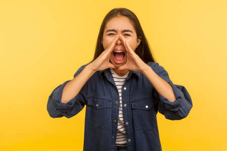 Attention, everyone listen! Portrait of angry girl in denim shirt shouting into hands shaped in megaphone, announcing negative message, loud voice. indoor studio shot isolated on yellow background Foto de archivo