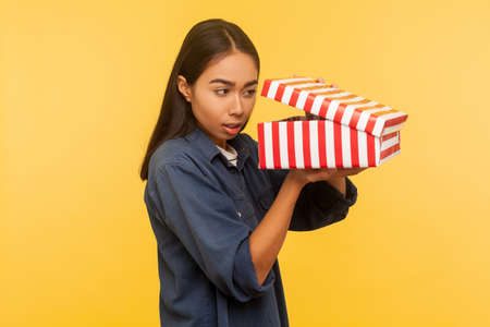 Portrait of curious funny girl in denim shirt opening gift and looking into box with interest, peeking inside in anticipation of nice present surprise. indoor studio shot isolated on yellow background
