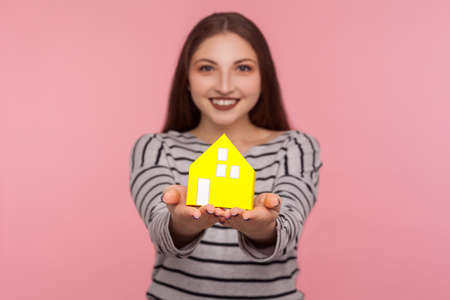 Portrait of cheerful young woman in striped sweatshirt showing paper house and looking at camera with toothy smile. studio shot isolated on pink background