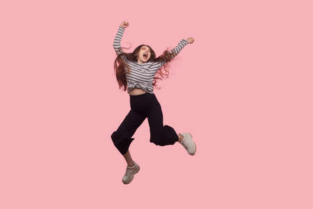 Portrait of enthusiastic, extremely happy woman shouting for joy and flying, jumping in air with raised fists, celebrating success. studio shot isolated, full length