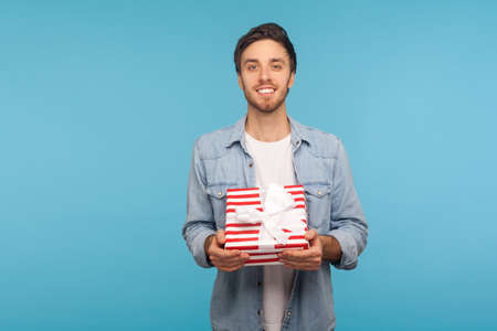 Portrait of happy handsome bristle man in stylish denim shirt holding gift and smiling to camera, showing birthday surprise, holiday bonus wrapped in box. studio shot isolated on blue background