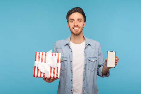 Portrait of handsome man in denim shirt holding gift box and cell phone with mock up, blank display for advertise. indoor studio shot isolated on blue background