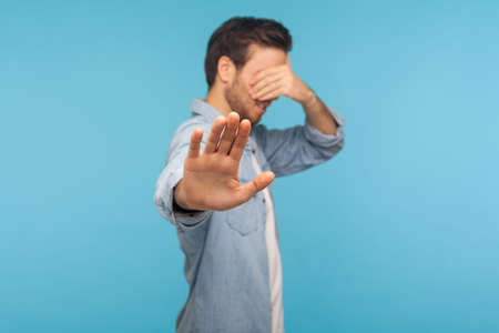 Portrait of confused shy man in worker denim shirt covering eyes showing stop gesture, refusing to look at shameful content, scared to see. indoor studio shot, blue background