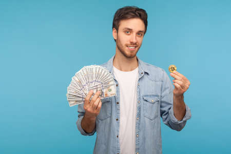 Happy handsome man in worker denim shirt showing dollar banknotes and bitcoin, looking at camera with toothy smile. studio shot isolated on blue background