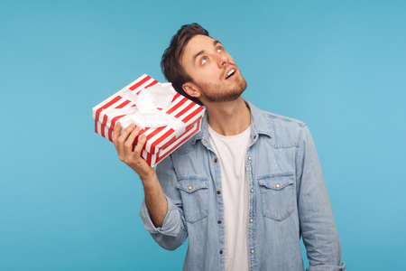 Portrait of young curious man in denim shirt holding gift box near ear and listening, guessing present, in anticipation of interesting birthday surprise. indoor studio shot isolated on blue background