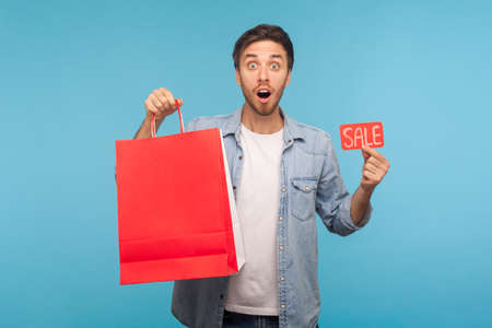 Portrait of surprised shopper man in denim shirt holding Sale inscription and packages with blank space for advertise text, discount in store, expressing shock. studio shot isolated on blue background