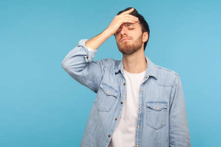 I forgot, my fault. Portrait of upset man in worker denim shirt standing with facepalm gesture, blaming himself, feeling sorrow regret because of bad memory. studio shot isolated on blue background