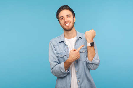 Portrait of cheerful punctual man in worker denim shirt pointing at wrist watch and smiling, showing smartwatch devise with mock up display. indoor studio shot isolated on blue background
