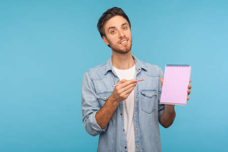 Portrait of positive man in worker denim shirt showing notebook with blank space for commercial text, advertising area on paper for plans, business idea. indoor studio shot isolated on blue background