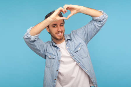 Portrait of handsome man with bristle in stylish denim shirt showing heart shape gesture and smiling romantically, flirting to camera. indoor studio shot isolated on blue background