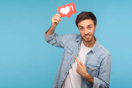 Portrait of cheerful handsome blogger man in denim shirt pointing at social media heart Like button, emoji counter, follower notification. indoor studio shot isolated on blue background 版權商用圖片