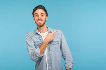 Portrait of handsome happy man in stylish denim shirt pointing aside, showing blank copy space for idea presentation, commercial text. indoor studio shot isolated on blue background