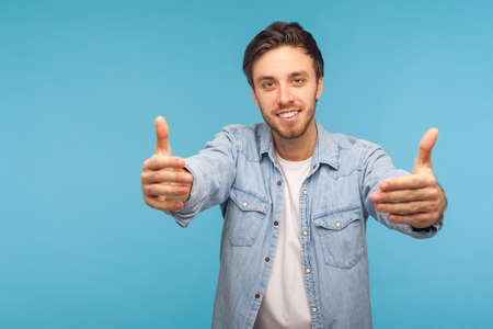 Portrait of handsome friendly good-natured man in worker denim shirt raising hands to embrace, inviting for free hugs and smiling kind. studio shot isolated on blue background