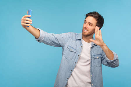 Portrait of friendly handsome man in denim shirt talking on video call and waving hello gesture, having online conversation on mobile phone, taking selfie. studio shot isolated on blue background